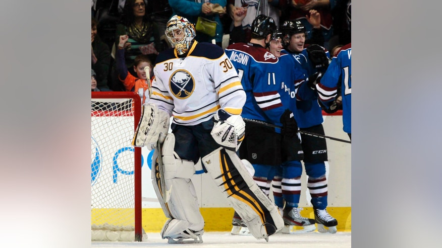 Buffalo Sabres goalie Ryan Miller (30) reacts after giving up a goal to Colorado Avalanche defenseman Tyson Barrie, back center, as he celebrates with teammates Jamie McGinn, back left, in the first period of an NHL hockey game in Denver, Saturday, Feb. 1, 2014. (AP Photo/David Zalubowski)