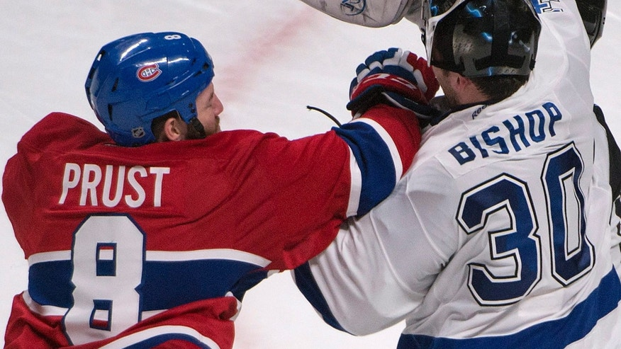 Tampa Bay Lightning goalie Ben Bishop gets a punch to the face during a break in play by Montreal Canadiens' Brandon Prust  during the second period of an NHL game in Montreal, Saturday, Feb. 1, 2014. (AP Photo/The Canadian Press, Peter McCabe)