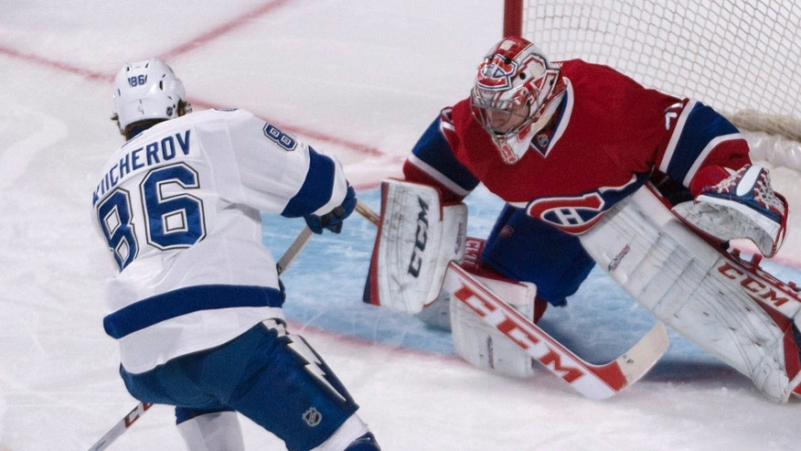 Montreal Canadiens goalie Carey Price eyes the puck as Tampa Bay Lightning Nikita Kucherov, of Russia, tries to score during a penalty shot in first period of an NHL game in Montreal Saturday, Feb. 1, 2014. (AP Photo/The Canadian Press, Peter McCabe)