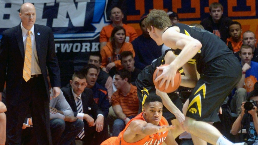 Illinois' Joseph Bertrand (2) hits the floor trying to take the ball away from Iowa center Adam Woodbury (34) during an NCAA college basketball game in Champaign, Ill., Saturday, Feb. 1, 2014. (AP Photo/Robin Scholz)