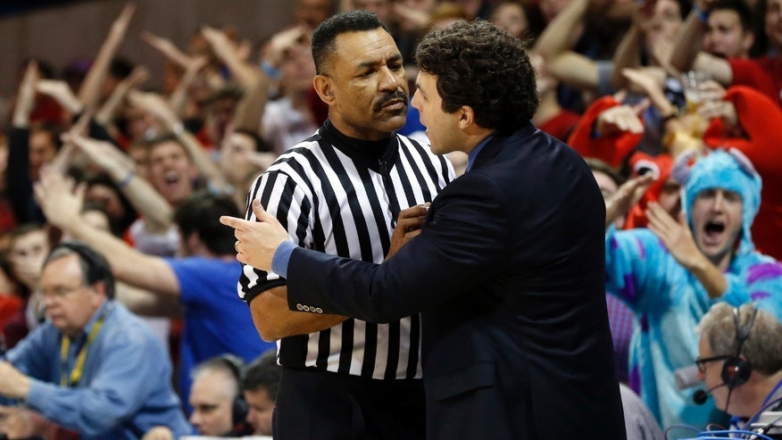 "Referee Jeff Clark restrains Memphis head coach Josh Pastner, as SMU fans signal with ""T"" hand signs, meaning they want a technical foul called, during the second half of a basketball game on Saturday, Feb. 1, 2014, in Dallas. No foul was called.  SMU won the game 87-72. (AP Photo/John F. Rhodes)"