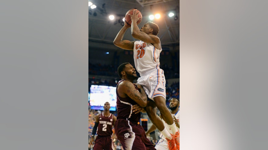 Florida guard Michael Frazier II (20) shoots over Texas A&M forward Kourtney Roberson (14) during the first half of an NCAA college basketball game, Saturday, Feb. 1, 2014, in Gainesville, Fla. (AP Photo/Phil Sandlin)