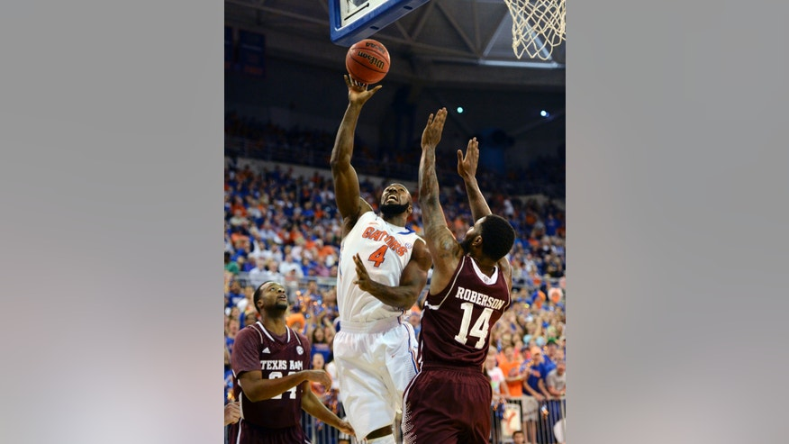 Florida center Patric Young (4) goes to the basket as Texas A&M forward Antwan Space (24) and Kourtney Roberson (14) try to block the shot during the first half of an NCAA college basketball game, Saturday, Feb. 1, 2014, in Gainesville, Fla. (AP Photo/Phil Sandlin)