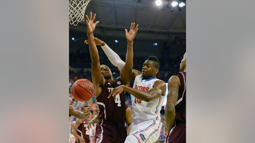 Florida forward Will Yeguete (15) loses the ball as Texas A&M forward Antwan Space (24) defends during the first half of an NCAA college basketball game, Saturday, Feb. 1, 2014, in Gainesville, Fla. (AP Photo/Phil Sandlin)