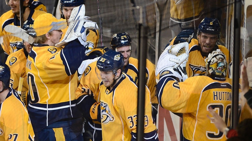 Nashville Predators defenseman Shea Weber (6), upper right, celebrates with his team and goalie Carter Hutton (30) after scoring the winning goal in overtime against the New Jersey Devils at an NHL hockey game on Friday, Jan. 31, 2014, in Nashville, Tenn. (AP Photo/Mark Zaleski)