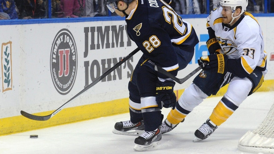 St. Louis Blues' Ian Cole (28) reaches for the puck next to Nashville Predators' Colin Wilson (33) during the first period of an NHL hockey game Saturday, Feb. 1, 2014, in St. Louis. (AP Photo/Bill Boyce)