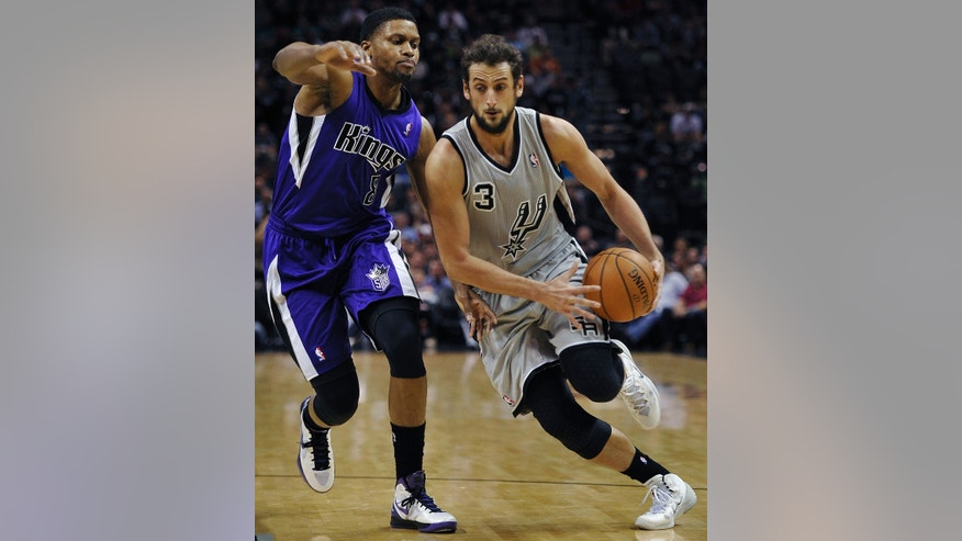 San Antonio Spurs guard Marco Belinelli, right, drives around Sacramento Kings forward Rudy Gay during the first half of an NBA basketball game, Saturday, Feb. 1, 2014, in San Antonio. (AP Photo/Darren Abate)