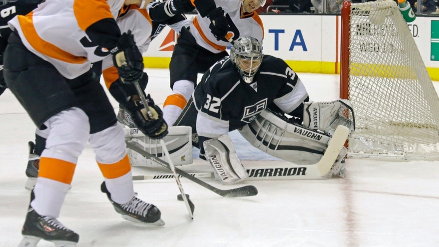 Los Angeles Kings goalie Jonathan Quick (32) defends as Philadelphia Flyers center Vincent Lecavalier (40) and center Brayden Schenn (10) approach in the first period of an NHL hockey game in Los Angeles Saturday, Feb. 1, 2014.  (AP Photo/Reed Saxon)