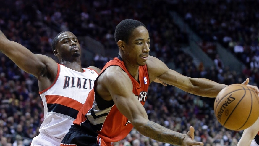 Toronto Raptors guard DeMar DeRozan, right, pulls in a loose ball as Portland Trail Blazers guard Wesley Matthews defends during the first half of an NBA basketball game in Portland, Ore., Saturday, Feb. 1, 2014.(AP Photo/Don Ryan)