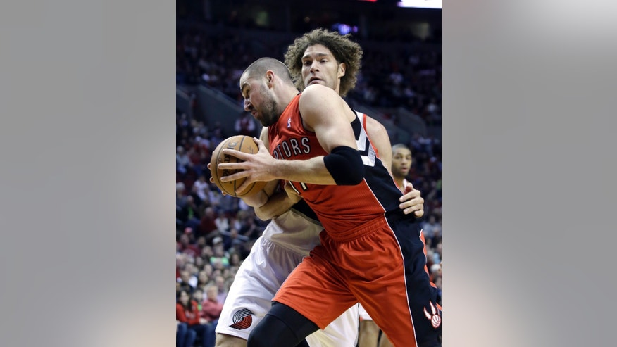 Toronto Raptors center Jonas Valanciunas, left, makes a drive on Portland Trail Blazers center Robin Lopez during the first half of an NBA basketball game in Portland, Ore., Saturday, Feb. 1, 2014. (AP Photo/Don Ryan)