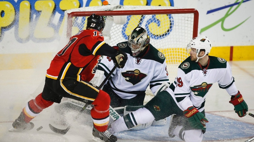 Minnesota Wild goalie Darcy Kuemper, center, kicks the puck away from Calgary Flames' Lance Bouma, left, with the help of teammate Stephane Veilleux during the second period of an NHL hockey game in Calgary, Alberta, Saturday, Feb. 1, 2014. (AP Photo/The Canadian Press, Jeff McIntosh)