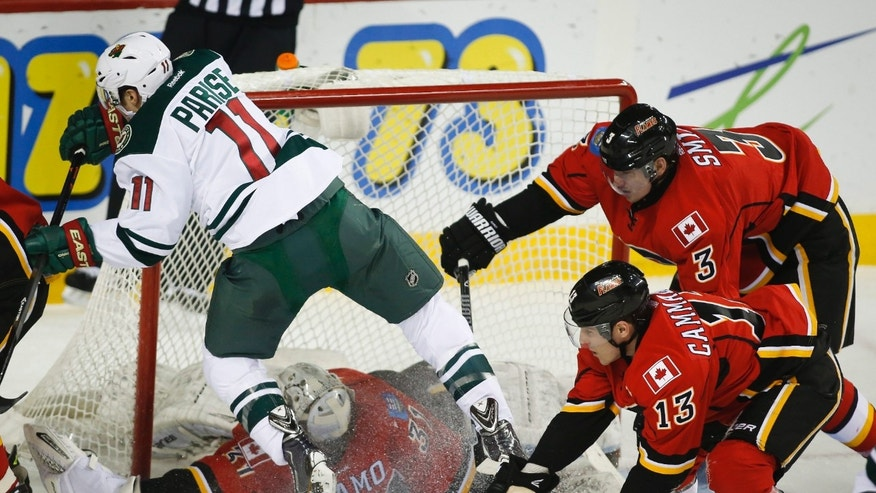 Minnesota Wild Zach Parise, center, gets slammed into the net by Calgary Flames' Ladislav Smid, right, from the Czech Republic, during the first period of an NHL hockey game, Saturday, Feb. 1, 2014 in Calgary, Alberta. (AP Photo/The Canadian Press, Jeff McIntosh)