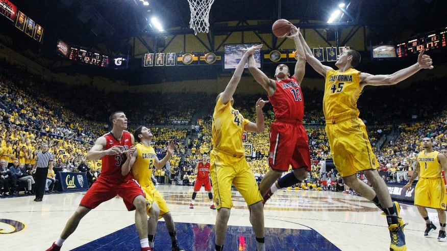 California forward David Kravish (45) blocks a shot attempt by Arizona guard Nick Johnson (13) during the first half on an NCAA college basketball game on Saturday, Feb. 1, 2014, in Berkeley, Calif. (AP Photo/Marcio Jose Sanchez)