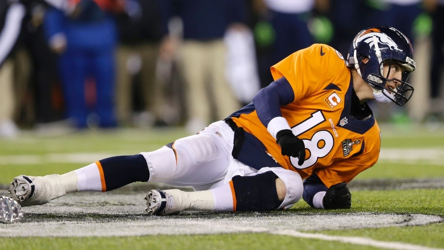 Denver Broncos' Peyton Manning lies on the ground after being tackled during the second half of the NFL Super Bowl XLVIII football game against the Seattle Seahawks Sunday, Feb. 2, 2014, in East Rutherford, N.J. (AP Photo/Julio Cortez)