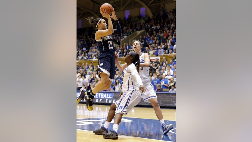 Notre Dame's Kayla McBride (21) drives to the basket as Duke's Alexis Jones and Haley Peters, right, defend during the second half of an NCAA college basketball game in Durham, N.C., Sunday, Feb. 2, 2014. Notre Dame won 88-67. (AP Photo/Gerry Broome)