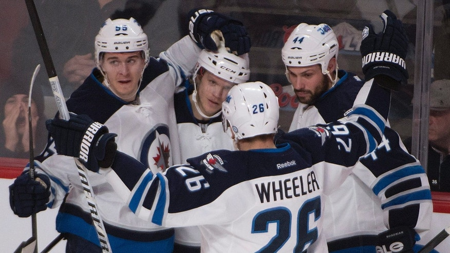 Winnipeg Jets' Tobias Enstrom, second from left, gets congratulated by teammates Mark Scheifele (55), Blake Wheeler (26) and Zach Bogosian (44) after scoring against the Montreal Canadiens during second period NHL action in Montreal, Sunday, Feb. 2, 2014. (AP Photo/The Canadian Press, Peter Mccabe)