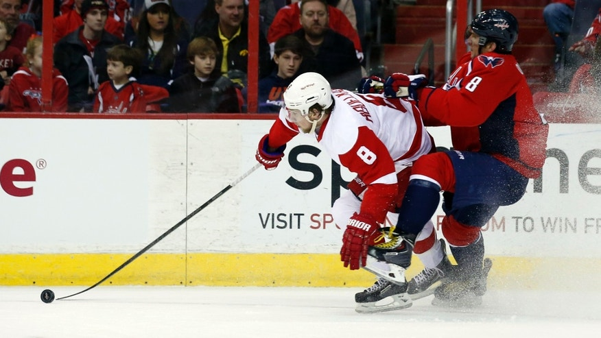 Detroit Red Wings left wing Justin Abdelkader, left, and Washington Capitals right wing Alex Ovechkin. right, from Russia, collide in the first period of an NHL hockey game on Sunday, Feb. 2, 2014, in Washington. (AP Photo/Alex Brandon)