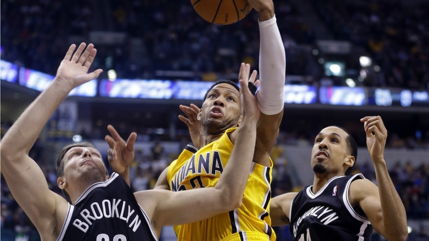 Indiana Pacers forward Paul George, center, grabs a rebound between Brooklyn Nets forward Mirza Teletovic, left, and guard Shaun Livingston in the second half of an NBA basketball game in Indianapolis, Saturday, Feb. 1, 2014. The Pacers defeated the Nets 97-96. (AP Photo/Michael Conroy)