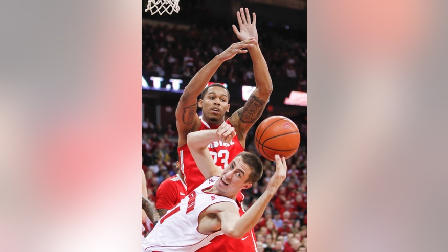 Ohio State's Amir Williams, top, knocks the ball away from Wisconsin's Josh Gasser during the second half of an NCAA college basketball game Saturday, Feb. 1, 2014, in Madison, Wis. Ohio State upset Wisconsin, 59-58. (AP Photo/Andy Manis)