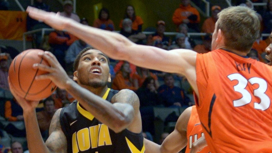 Iowa's guard Roy Devyn Marble (4)  is guarded by Illinois' Jon Ekey (33) during an NCAA college basketball game in Champaign, Ill., Saturday, Feb. 1, 2014. (AP Photo/Robin Scholz)