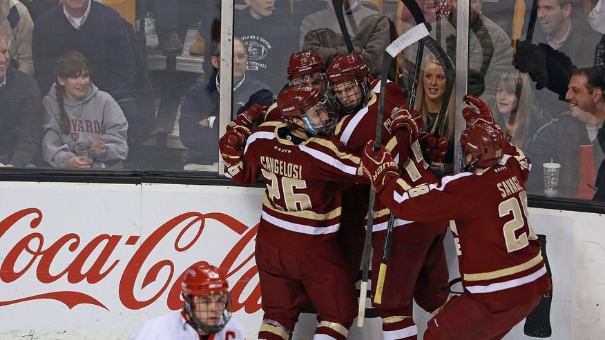 Boston College's Ryan Fitzgerald, center, is congratulated by teammates Austin Cangelosi, left, Adam Gilmour and Scott Savage after Fitzgerald's his first period goal against Boston University in the Beanpot college hockey tournament game in Boston, Monday, Feb. 3, 2014. (AP Photo/The Boston Herald, Matthew West) BOSTON GLOBE OUT; METRO BOSTON OUT; MAGS OUT; ONLINE OUT