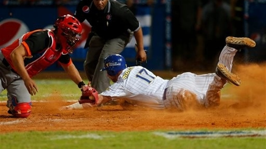 Venezuela's outfielder Lew Ford, right, slides safe onto home plate and scoring a run as Cuba's catcher Yulexis La Rosa tries to tagged out during a Caribbean Series baseball game in Porlamar, Venezuela, Monday, Feb. 3, 2014. Venezuela won the game 8-5.(AP Photo/Fernando Llano)