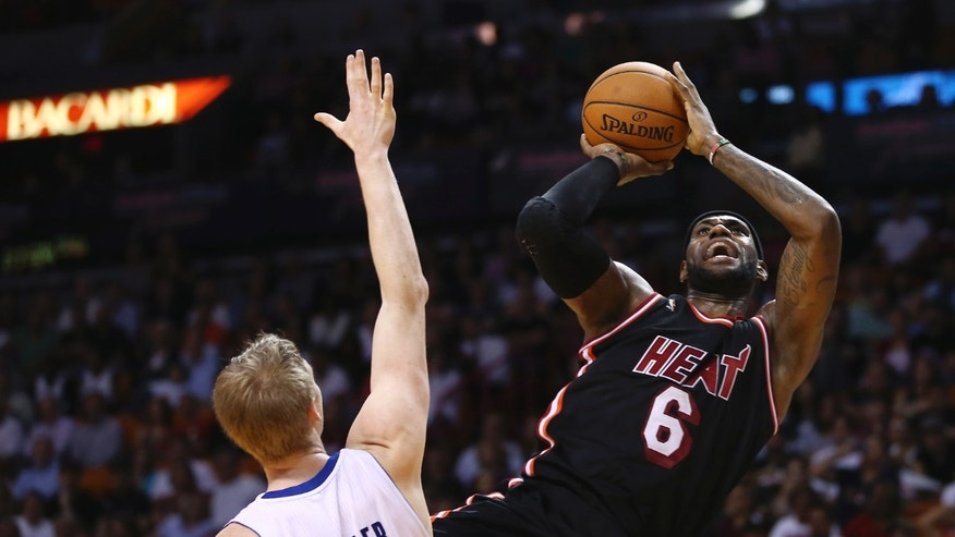 Detroit Pistons' Kyle Singler (25) tries to block Miami Heat's LeBron James (6) during the first half of a NBA basketball game in Miami, Monday, Feb. 3, 2014. (AP Photo/J Pat Carter)