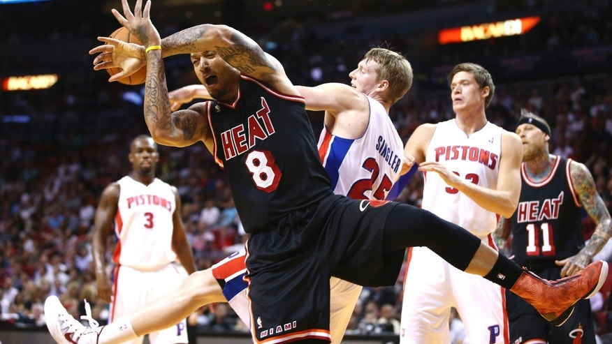 Miami Heat's Michael Beasley (8) and Detroit Pistons' Kyle Singler (25) fight for control of the ball during the first half of a NBA basketball game in Miami, Monday, Feb. 3, 2014. (AP Photo/J Pat Carter)