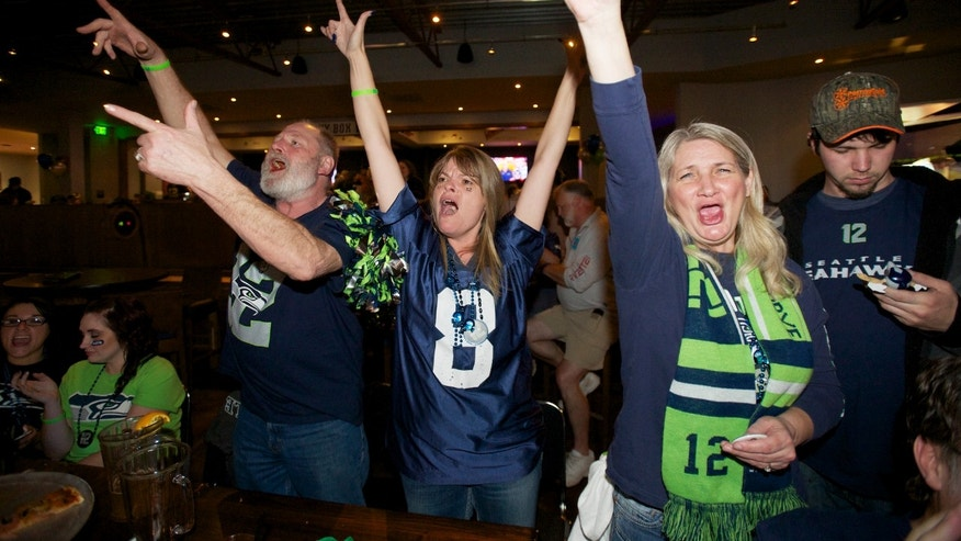 Seahawks fans from left, Ron Taylor, Michelle Taylor and Vienna Creighton celebrate while watching Super Bowl XLVIII at Big Al's in Vancouver, Wash., Sunday, Feb. 2, 2014. Seattle defeated the Denver Broncos 43-8. (AP Photo/The Columbian, Steven Lane)