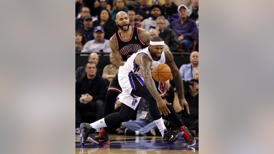 Sacramento Kings center DeMarcus Cousin, right, looses the ball as Chicago Bulls forward Carlos Boozer looks on during the first quarter of an NBA basketball game in Sacramento, Calif., Monday, Feb. 3, 2014. (AP Photo/Rich Pedroncelli)