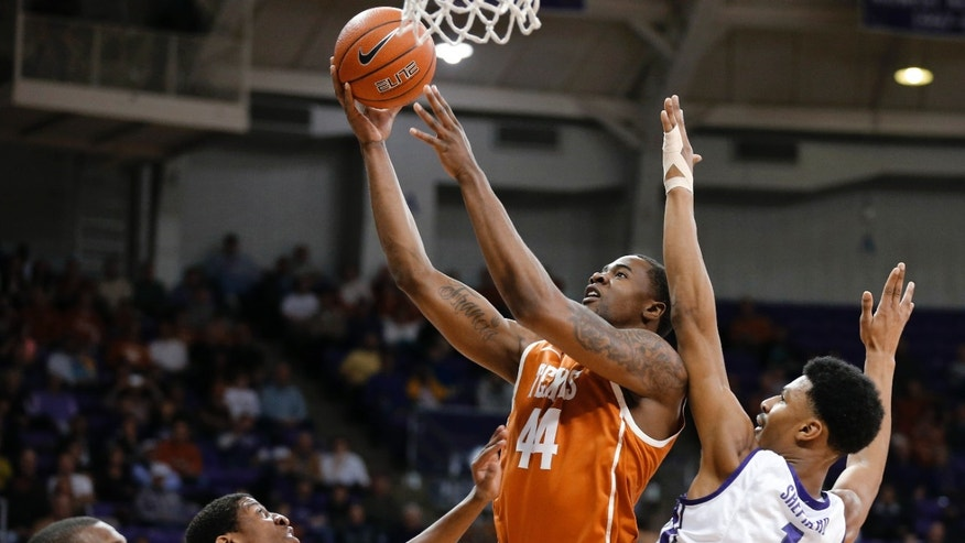 Texas center Prince Ibeh (44) takes a shot while forward Jonathan Holmes (10) watches and TCU guard Jarvis Ray (22) and center Karviar Shepherd (1) defend during the first half of an NCAA college basketball game Tuesday, Feb. 4, 2014, in Fort Worth, Texas. (AP Photo/Sharon Ellman)