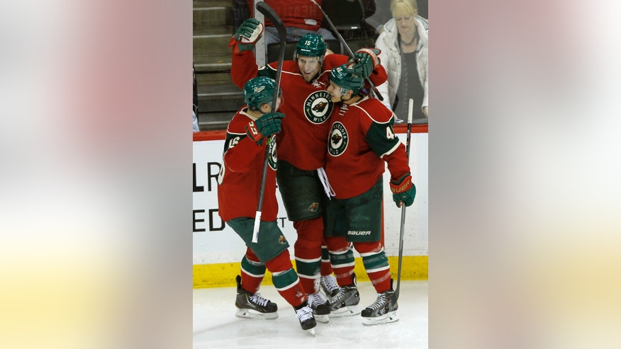 Minnesota Wild left wing Jason Zucker, left, and defenseman Jared Spurgeon, right, congratulate left wing Dany Heatley, center, after his goal on Tampa Bay Lightning goalie Ben Bishop during the third period of an NHL hockey game in St. Paul, Minn., Tuesday, Feb. 4, 2014. The Wild won 2-1. (AP Photo/Ann Heisenfelt)