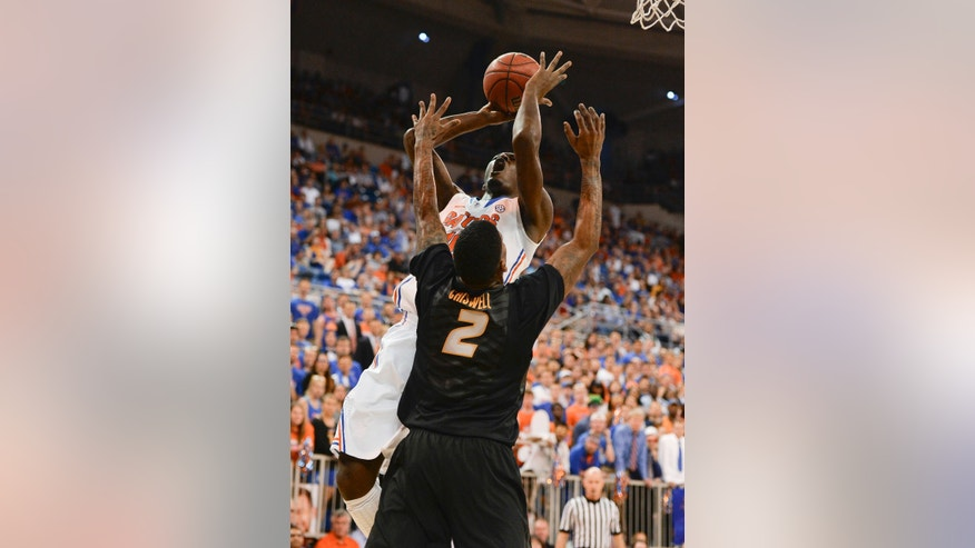 Florida forward Dorian Finney-Smith (10) tries to get the ball to the basket as Missouri forward Tony Criswell (2) defends during the first half of an NCAA college basketball game Tuesday, Feb. 4, 2014, in Gainesville, Fla. (AP Photo/Phil Sandlin)