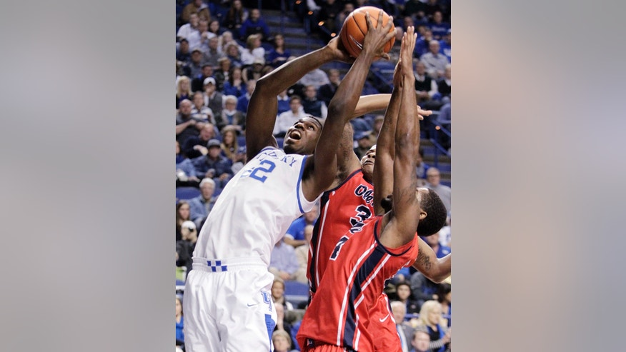 CORRECTS DAY TO TUESDAY Kentucky's Alex Poythress, left, looks for an opening on Mississippi's Jarvis Summers and Aaron Jones, right, during the first half of an NCAA college basketball game, Tuesday, Feb. 4, 2014, in Lexington, Ky. (AP Photo/James Crisp)