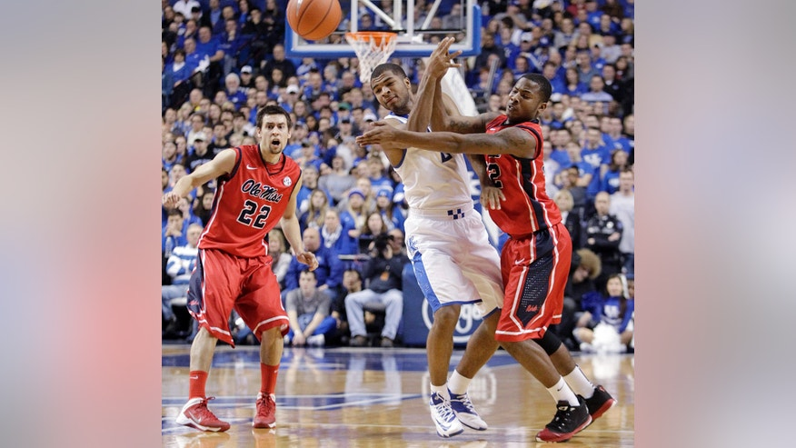 CORRECTS DAY TO TUESDAY Kentucky's Aaron Harrison, middle, has the ball knocked away between Mississippi's Marshall Henderson (22) and Jarvis Summers during the first half of an NCAA college basketball game, Tuesday, Feb. 4, 2014, in Lexington, Ky. (AP Photo/James Crisp)
