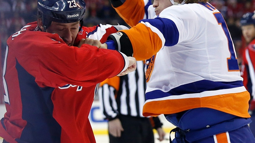 Washington Capitals defenseman Tyson Strachan (23) and New York Islanders left wing Matt Martin (17) fight in the first period of an NHL hockey game, Tuesday, Feb. 4, 2014, in Washington. (AP Photo/Alex Brandon)