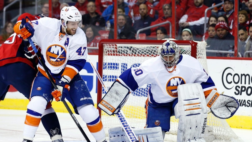 New York Islanders defenseman Andrew MacDonald (47) clears the puck as goalie Evgeni Nabokov (20), from Russia, watches in the first period of an NHL hockey game against the Washington Capitals, Tuesday, Feb. 4, 2014, in Washington. (AP Photo/Alex Brandon)