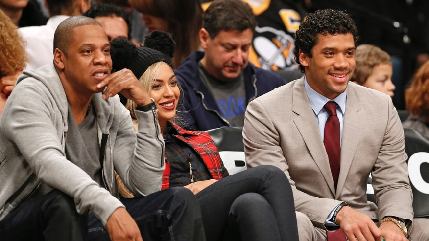 Rapper Jay Z, left, sits beside his wife Beyonce, and Seattle Seahawks quarterback Russell Wilson, right, as they watch the Brooklyn Nets NBA basketball game against the Philadelphia 76ers at the Barclays Center, Monday, Feb. 3, 2014 in New York. (AP Photo/Kathy Willens)