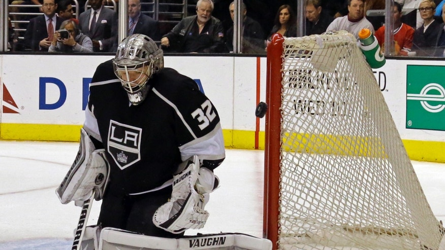 Los Angeles Kings goalie Jonathan Quick (32) deflects the puck off against the Chicago Blackhawks in the first period of an NHL hockey game in Los Angeles, Monday, Feb. 3, 2014. (AP Photo/Reed Saxon)