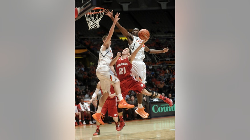Wisconsin guard Josh Gasser (21) puts up a shot between Illinois' Jon Ekey (33) and Nnanna Egwu (32) during the second half of an NCAA college basketball game Tuesday, Feb. 4, 2014, in Champaign, Ill. (AP Photo/Rick Danzl)