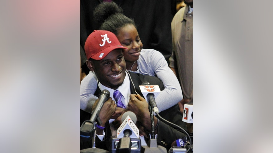 Rashaan Evans gets a big hug from his little sister, Ashley Evans, after the Auburn High School football player announced that he will attend Alabama during a national signing day ceremony on Wednesday, Feb. 5, 2014, in Auburn, Ala. (AP Photo/Butch Dill)