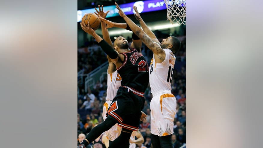Chicago Bulls' Taj Gibson, center, shoots over Phoenix Suns' Markieff Morris, right, during the first half of an NBA basketball game, Tuesday, Feb. 4, 2014, in Phoenix. (AP Photo/Matt York)