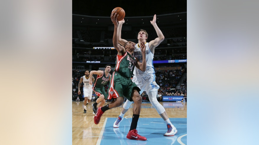 Milwaukee Bucks forward Giannis Antetokounmpo, front, of Greece, has his shot blocked by Denver Nuggets center Timofey Mozgov, of Russia, in the first quarter of an NBA basketball game in Denver, Wednesday, Feb. 5, 2014. (AP Photo/David Zalubowski)