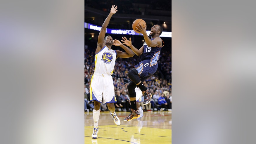 Charlotte Bobcats' Kemba Walker (15) scores against Golden State Warriors' Harrison Barnes (40) during the first half of an NBA basketball game in Oakland, Calif., Tuesday, Feb. 4, 2014. (AP Photo/Tony Avelar)