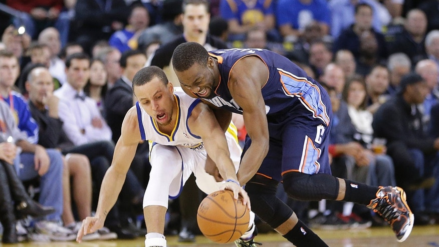 Charlotte Bobcats' Kemba Walker (15) battles for a loose ball against Golden State Warriors' Stephen Curry (30) during the first half of an NBA basketball game in Oakland, Calif., Tuesday, Feb. 4, 2014. (AP Photo/Tony Avelar)
