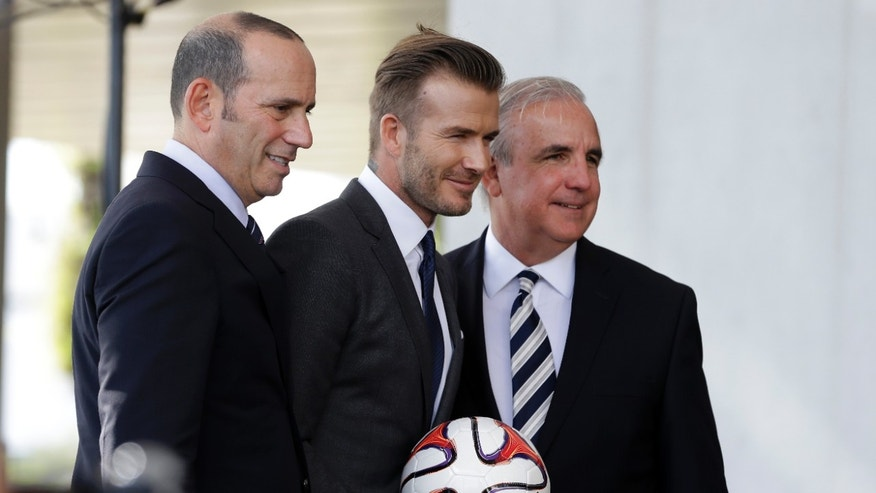 Former England soccer star David Beckham, center, poses with MLS Commissioner  Don Garber, left, and Miami-Dade County Mayor Carlos Gimenez, during a news conference where Beckham announced he will exercise his option to purchase a Major League Soccer expansion team in Miami, Wednesday, Feb. 5,  2014, in Miami. (AP Photo/Lynne Sladky)