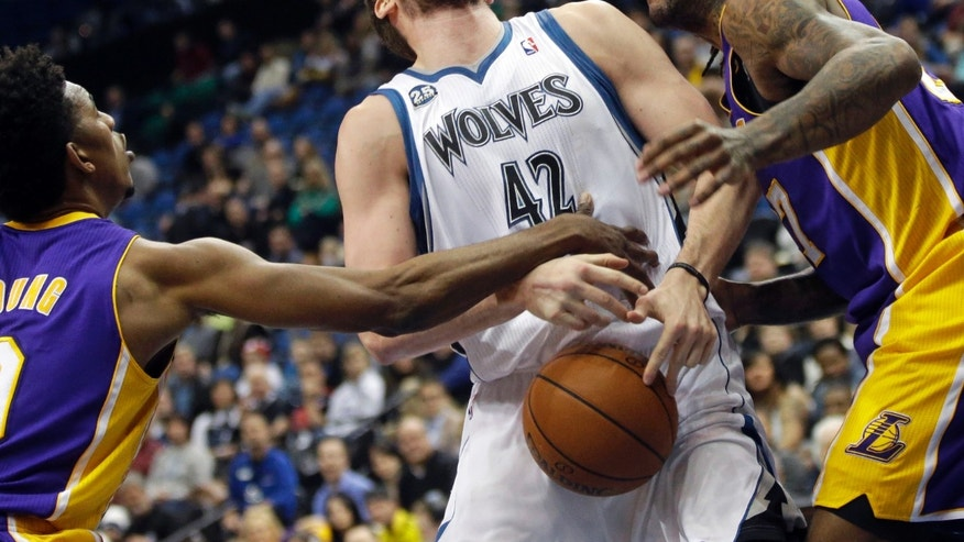 Minnesota Timberwolves' Kevin Love, center, loses the ball as he is fouled by Los Angeles Lakers' Nick Young, left, as Young and Jordan Hill defend during the first quarter of an NBA basketball game, Tuesday, Feb. 4, 2014, in Minneapolis. (AP Photo/Jim Mone)