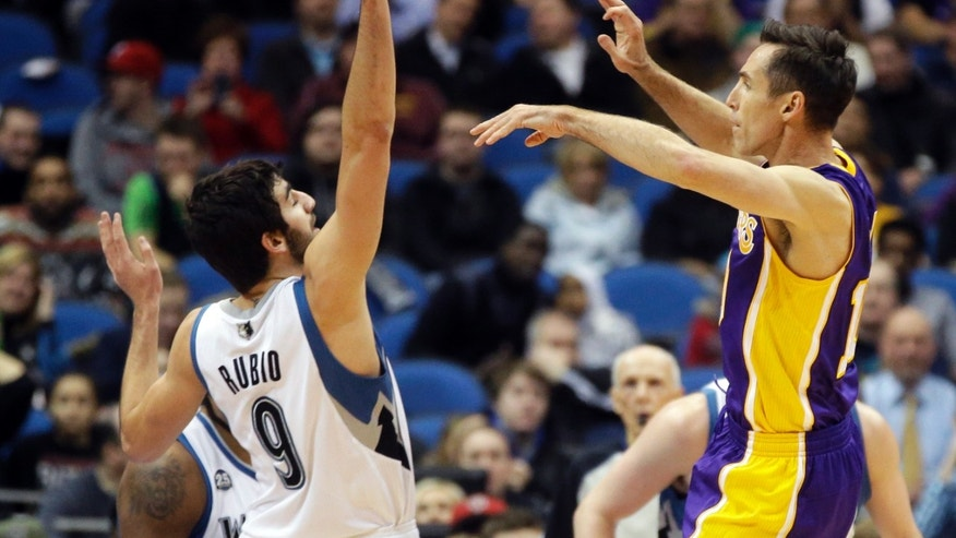Los Angeles Lakers' Steve Nash, right, makes a pass over Minnesota Timberwolves' Ricky Rubio, of Spain, during the first quarter of an NBA basketball game, Tuesday, Feb. 4, 2014, in Minneapolis. It was Nash's first game since Nov. 10, as he recovered from a back injury. (AP Photo/Jim Mone)