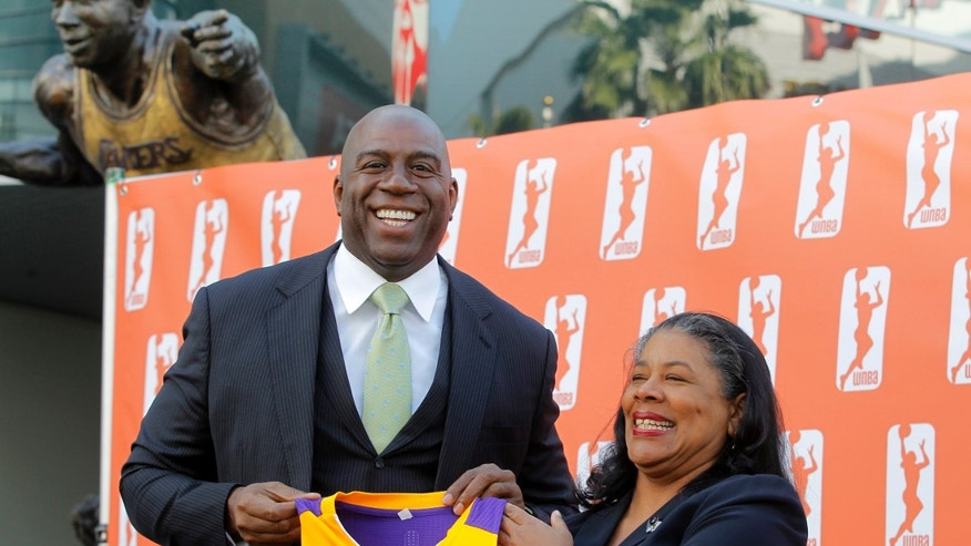 Former Los Angeles Laker Magic Johnson is joined by WNBA president Laurel Richie, as they pose for photographers after a news conference in front of Staples Center in Los Angeles on Wednesday, Feb 5, 2014. Johnson is part of a group buying the Los Angeles Sparks of the WNBA. At upper left is a statue of Johnson. (AP Photo/Nick Ut)