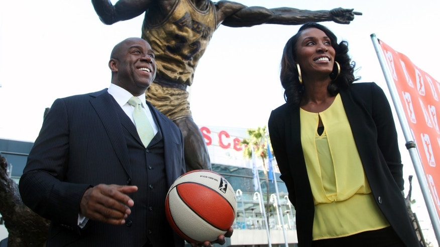 Former Los Angeles Laker Magic Johnson is joined by former Los Angeles Sparks' Lisa Leslie under a statue of Johnson after a news conference at Staples Center in Los Angeles on Wednesday, Feb 5, 2014. Johnson is part of a group buying the Sparks of the WNBA. (AP Photo/Nick Ut)